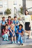 Grupo de alumnos elementales fuera de la sala de clase con el profesor Foto de archivo libre de regalías