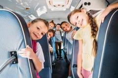 grupo de alumnos lindos que montan en el autobús escolar y la mirada imágenes de archivo libres de regalías