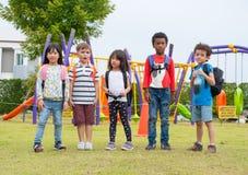 Grupo de alunos da diversidade que jogam no campo de jogos no tipo Foto de Stock