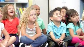 Grupo de alunos elementares da idade que sentam-se no assoalho