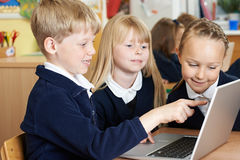 Grupo de alunos elementares que trabalham junto no computador foto de stock royalty free