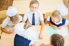 Grupo de alunos na sala de aula da escola que senta-se na mesa Imagens de Stock Royalty Free