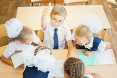 Grupo de alunos na sala de aula da escola que senta-se na mesa Fotografia de Stock