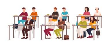 Grupo de alunos que sentam-se em mesas na sala de aula, demonstrando o bom comportamento e escutando atentamente a lição ou ilustração stock