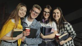 Grupo de amigo que se coloca juntos que sostiene los libros metrajes