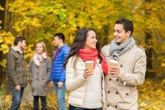 Grupo de amigo sonriente con las tazas de café en parque Foto de archivo libre de regalías