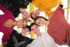 Grupo de amigos abrazados en círculo Foto de archivo