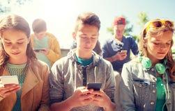 Grupo de amigos adolescentes con smartphones al aire libre Fotos de archivo libres de regalías