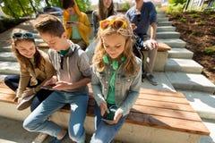 Grupo de amigos adolescentes con smartphones al aire libre Foto de archivo libre de regalías