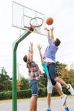 Grupo de amigos adolescentes felices que juegan a baloncesto Foto de archivo libre de regalías