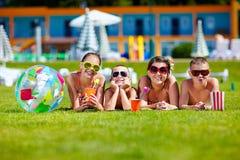 Grupo de amigos adolescentes felices que mienten en césped del verano Foto de archivo libre de regalías