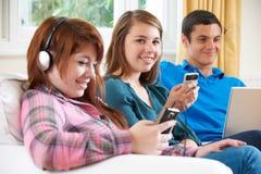 Grupo de amigos adolescentes que apreciam a tecnologia em casa imagens de stock