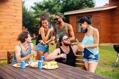 Grupo de amigos adolescentes que beben la cerveza y que comen los bocados Fotografía de archivo libre de regalías