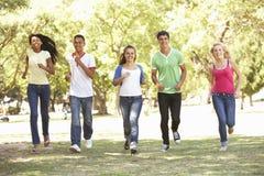 Grupo de amigos adolescentes que corren en parque Fotos de archivo