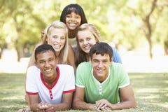 Grupo de amigos adolescentes que se divierten en parque Foto de archivo libre de regalías