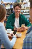 Grupo de amigos adolescentes que se encuentran en café y que usan los teléfonos móviles Fotos de archivo libres de regalías
