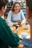 Grupo de amigos adolescentes que se encuentran en café y que usan los teléfonos móviles Fotografía de archivo libre de regalías