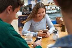 Grupo de amigos adolescentes que se encuentran en café y que usan los teléfonos móviles Fotos de archivo