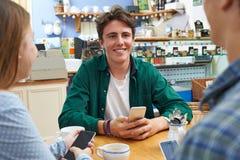 Grupo de amigos adolescentes que se encuentran en café y que usan los teléfonos móviles Foto de archivo libre de regalías