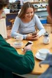 Grupo de amigos adolescentes que se encuentran en café y que usan los teléfonos móviles Fotografía de archivo