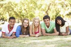Grupo de amigos adolescentes que se relajan en parque junto Imagen de archivo