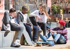 Grupo de amigos adolescentes que se relajan y que charlan Imagenes de archivo