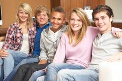 Grupo de amigos adolescentes que se sientan en el sofá en el país Foto de archivo libre de regalías