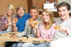 Grupo de amigos adolescentes que se sientan en el sofá en el país Fotos de archivo libres de regalías