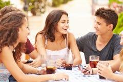 Grupo de amigos adolescentes que se sientan junto en el ½ del ¿de Cafï Imagenes de archivo