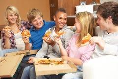 Grupo de amigos adolescentes que sentam-se no sofá em casa fotos de stock royalty free
