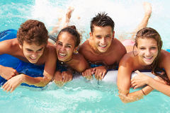 Grupo de amigos adolescentes que têm o divertimento na piscina Fotografia de Stock Royalty Free