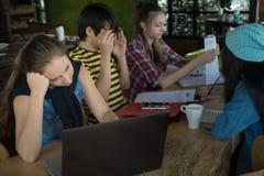 Grupo de amigos adolescentes que trabajan y que se encuentran en equipo con informes y ordenador portátil en la tabla de madera fotografía de archivo libre de regalías