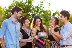 Grupo de amigos adolescentes que tuestan a una muchacha del cumpleaños Imagenes de archivo