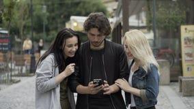 Grupo de amigos adolescentes que usam o smartphone para o entretenimento no ambiente urbano que tem o divertimento video estoque