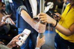 Grupo de amigos adultos jovenes que usan smartphones en el subterráneo Foto de archivo