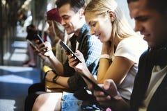 Grupo de amigos adultos jovenes que usan smartphones en el subterráneo Fotos de archivo libres de regalías