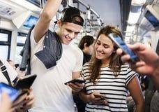 Grupo de amigos adultos jovenes que usan smartphones en el subterráneo Imagen de archivo libre de regalías