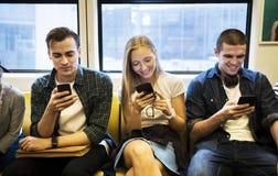 Grupo de amigos adultos jovenes que usan smartphones en el subterráneo Imagen de archivo