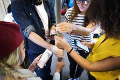 Grupo de amigos adultos jovenes que usan smartphones en el subterráneo Foto de archivo libre de regalías