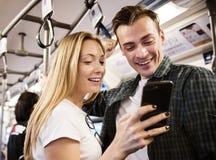 Grupo de amigos adultos jovenes que usan smartphones en el subterráneo Imagenes de archivo