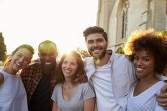 Grupo de amigos adultos jovenes sonrientes que abrazan en la calle Imagen de archivo libre de regalías