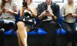Grupo de amigos adultos novos que usam smartphones no metro Foto de Stock