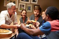 Grupo de amigos adultos que comen la pizza en un partido de casa Fotos de archivo