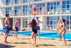 Grupo de amigos alegres de los pares que juegan a voleibol Imagen de archivo