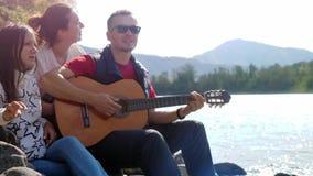 Grupo de amigos alegres en la playa que juega la canción del canto de la guitarra en un día de verano al lado del río de la monta almacen de video