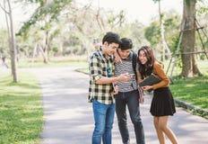 Grupo de amigos alegres que olham o telefone esperto exterior imagem de stock royalty free