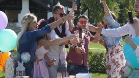 Grupo de amigos alegres que tienen un partido en el confeti que lanza de la ciudad y que beben el champán metrajes