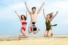 Grupo de amigos asiáticos que têm o divertimento e para saltar junto na praia imagens de stock royalty free