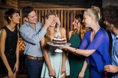 Grupo de amigos asombrosamente una mujer con la torta de cumpleaños Foto de archivo libre de regalías