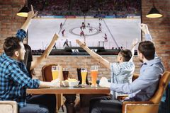 Grupo de amigos bonitos novos que olham a tevê e que cheering para sua equipe ao descansar no bar imagens de stock